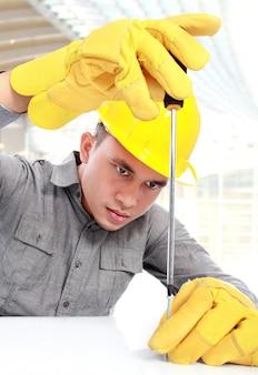 Jeune travailleur avec casque jaune