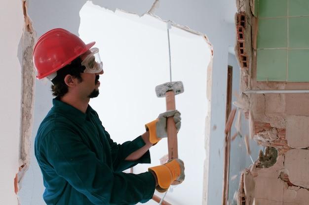 Jeune travailleur avec un casque de protection rouge et portant un costume bleu chaudière. concept de démolition