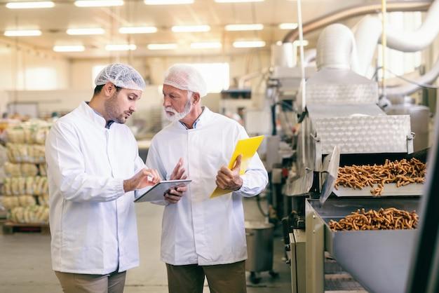 Jeune travailleur caucasien montrant à son collègue plus âgé statistique sur tablette en se tenant debout dans une usine alimentaire.