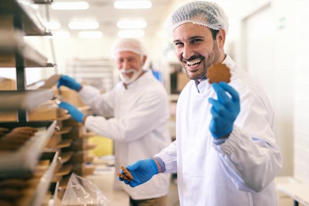 Jeune travailleur caucasien souriant montrant cookie en se tenant debout dans l'usine alimentaire.