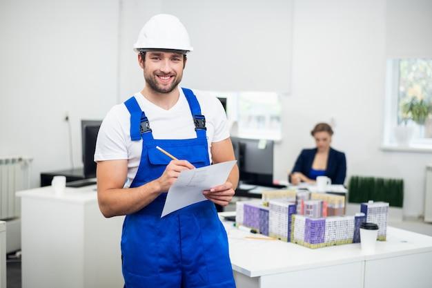 Un jeune travailleur de la construction souriant, prendre des notes dans le bureau