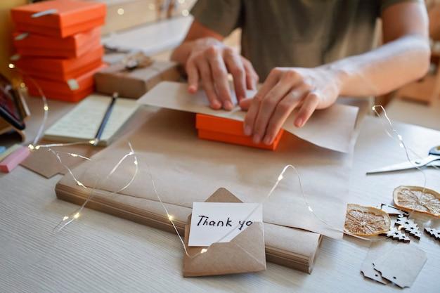 Jeune travailleur emballant des coffrets cadeaux de noël pour les clients famille petite entreprise travail à distance à domicile