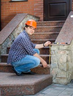 Jeune travailleur entrepreneur mesurant l'escalier en pierre avec un ruban à mesurer
