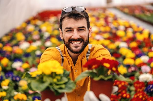 Jeune travailleur de jardin de pépinière souriant donnant des pots avec des fleurs