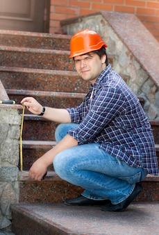 Jeune travailleur masculin souriant mesurant l'escalier en pierre avec un ruban à mesurer