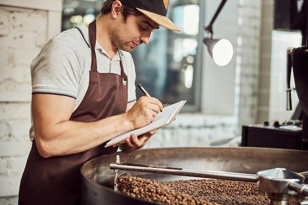 Jeune travailleur masculin en tablier écrit sur le presse-papiers en se tenant debout près du plateau de refroidissement avec des grains de café torréfiés