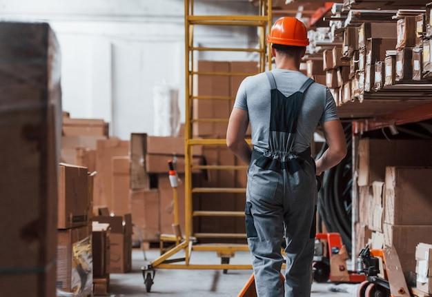 Un jeune travailleur masculin en uniforme est dans l'entrepôt avec un transpalette.