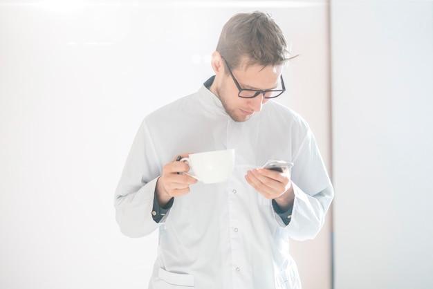 Un jeune travailleur médical masculin, médecin en uniforme blanc, médecin confiant