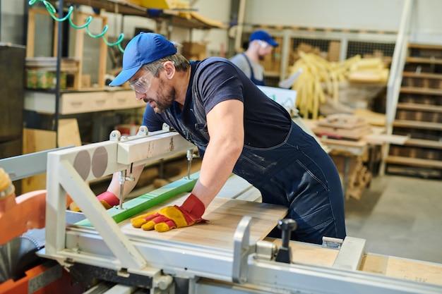 Jeune travailleur de meubles fixation planche de bois