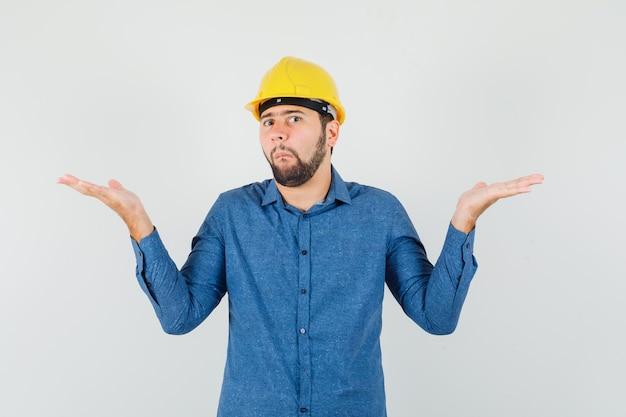 Jeune travailleur montrant un geste impuissant en chemise, casque et à la confusion