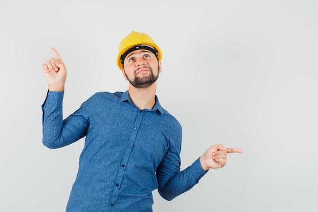Jeune travailleur pointant vers l'extérieur en chemise, casque et à la recherche d'espoir.
