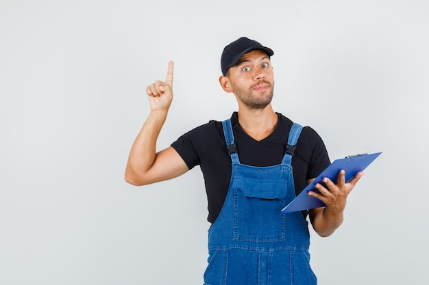 Jeune travailleur pointant vers le haut et tenant le presse-papiers en uniforme, vue de face.
