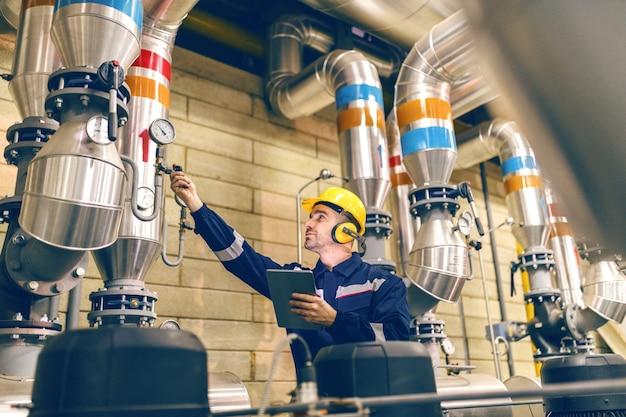 Jeune travailleur de race blanche en tenue de protection serrant la valve et à l'aide de comprimés en se tenant debout dans une usine de chauffage.