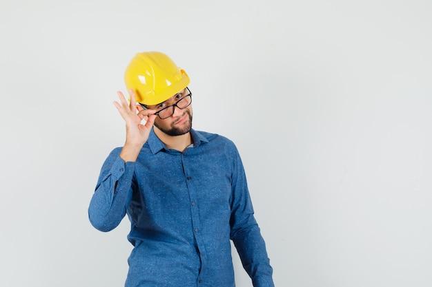 Jeune travailleur à la recherche de lunettes en chemise, casque et à la confiance.