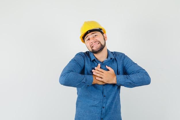 Jeune travailleur satisfait d'un compliment ou d'un cadeau en chemise, casque et à la recherche de reconnaissance.