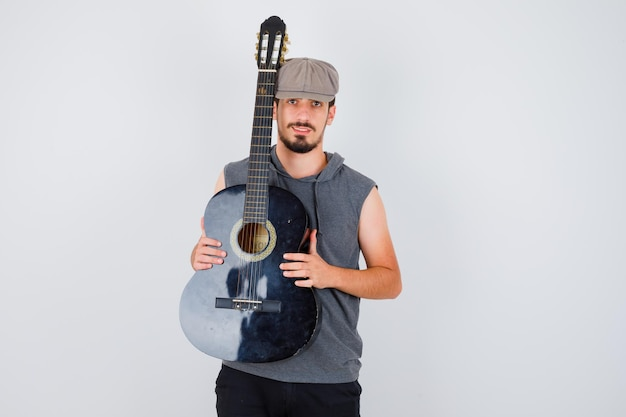 Jeune travailleur tenant une guitare avec les deux mains en t-shirt et casquette gris et ayant l'air heureux