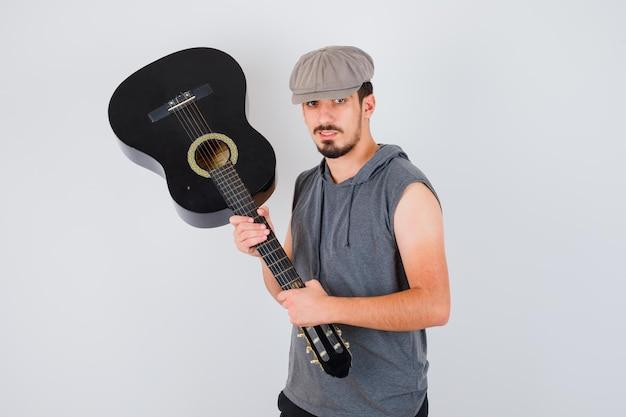 Jeune travailleur tenant une guitare avec les deux mains en t-shirt gris et casquette et à la recherche de sérieux