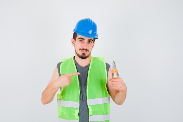 Jeune travailleur tenant des pinces et pointant vers lui en uniforme de construction et ayant l'air heureux