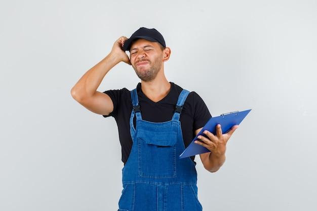 Jeune travailleur tenant le presse-papiers tout en touchant la tête avec la main en uniforme et à la recherche de regret. vue de face.