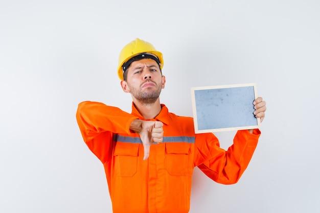 Jeune travailleur tenant tableau noir, montrant le pouce vers le bas en uniforme, casque et à la recherche de mécontentement.