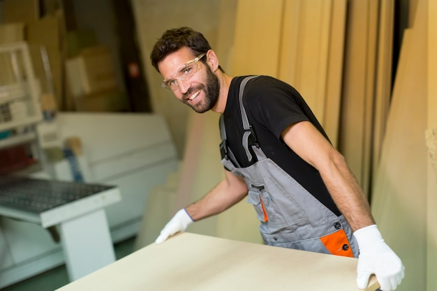 Jeune travailleur travaille dans une usine pour la production de meubles