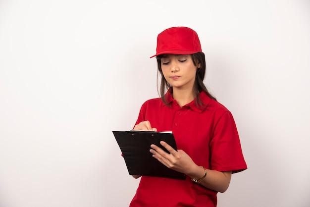 Jeune travailleur avec uniforme rouge et presse-papiers sur fond blanc.