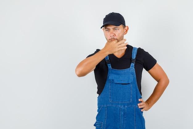 Jeune travailleur en uniforme sifflant avec la main sur la taille, vue de face.