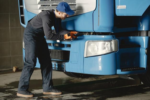 Un jeune travailleur vérifie la roue. dysfonctionnement du camion. travaux de service.