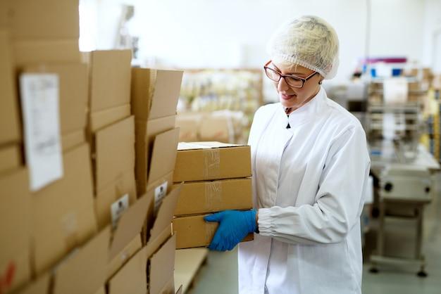 Une jeune travailleuse assez joyeuse dans des tissus stériles place une pile de boîtes sur une plus grande pile de boîtes en carton dans la zone de stockage de l'emballage d'usine.