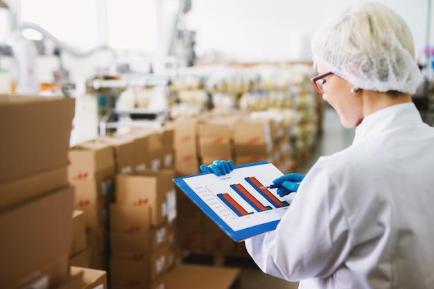 Une jeune travailleuse en chiffons stériles blancs vérifie les tableaux en se tenant debout dans une salle de stockage remplie de piles de boîtes.