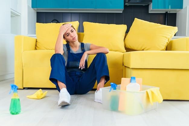 Jeune travailleuse du service de nettoyage assise près du canapé et se sentant fatiguée après avoir lavé le sol dans la cuisine.