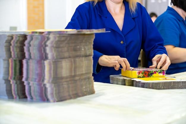 Jeune travailleuse emballant des boîtes pour expédition dans un entrepôt.