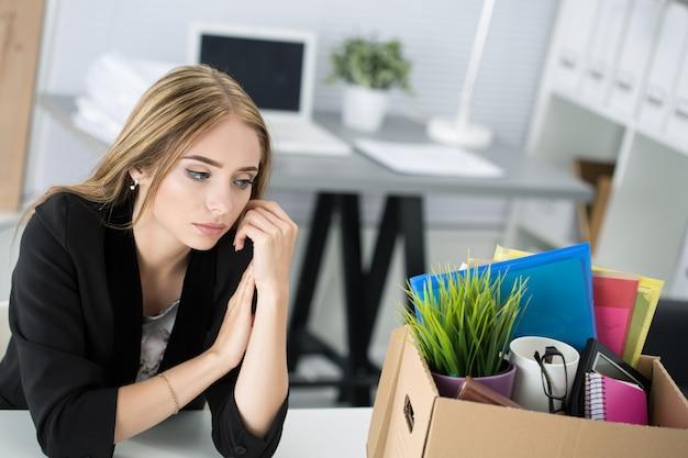 Jeune travailleuse licenciée au bureau assis près d'une boîte en carton avec ses effets personnels. être viré concept.