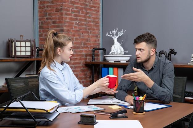 Jeune travailleuse et son collègue masculin assis à la table en train de réfléchir à une question importante au bureau