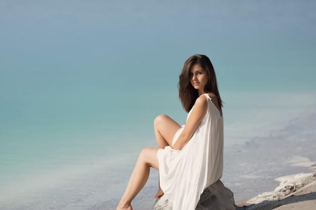 Jeune très belle fille aux cheveux longs dans une robe blanche au bord du lac.