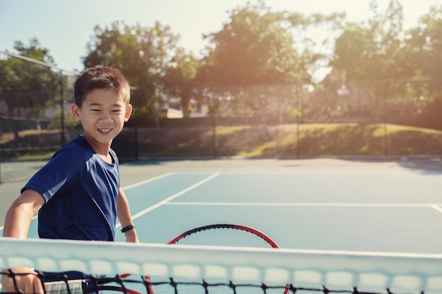 Jeune tween garçon de tennis asiatique sur la cour bleue extérieure