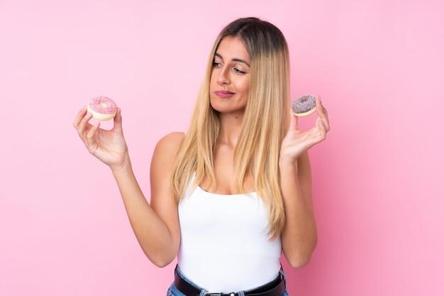 Jeune, uruguayen, femme, isolé, rose, mur, tenue, beignets