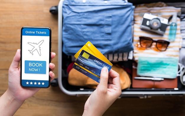Jeune utilisant des cartes de crédit avec smartphone pour le paiement du billet ou la réservation