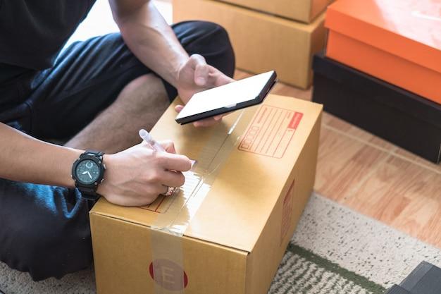 Jeune vendeur en ligne masculin à l'aide de smartphone et d'écrire l'adresse sur une boîte en carton.
