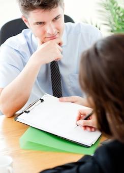 Jeune vendeur en regardant les clientes signent un contrat