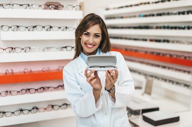 Jeune vendeuse heureuse et souriante travaillant dans un magasin d'optique. elle sourit et tient des lunettes tout en regardant la caméra.