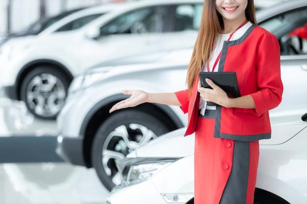 Jeune vendeuse de voitures asiatiques tenant la calculatrice avec un écran de bienvenue dans la salle d'exposition.