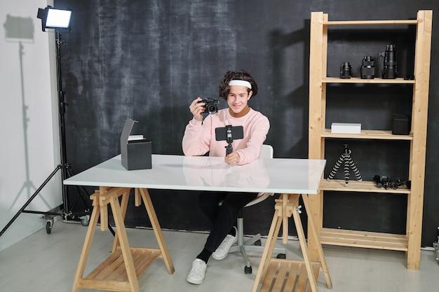 Jeune vlogger masculin occasionnel assis par bureau et montrant une photocamera tout en se tirant sur un smartphone en studio