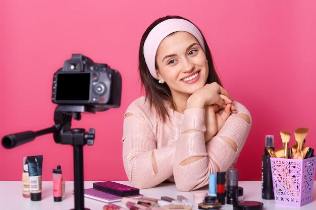 Une jeune vlogueuse de race blanche, a une conversation en ligne avec ses abonnés, réalise une vidéo pour un blog de beauté