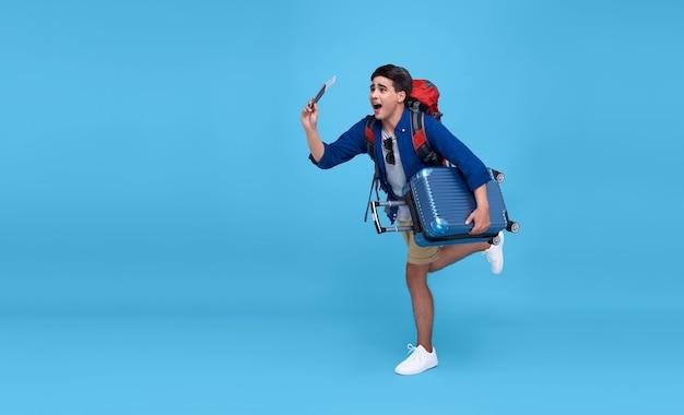 Jeune voyageur asiatique excité en cours d'exécution avec passeport sac à dos et carte d'embarquement prêt à voler sur bleu isolé.