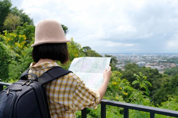 Jeune voyageur asiatique fille debout avec sac à dos et carte