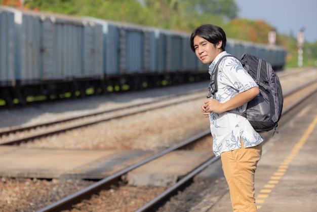 Jeune voyageur asiatique avec sac à dos dans le chemin de fer, sac à dos et chapeau à la gare avec un voyageur, concept de voyage