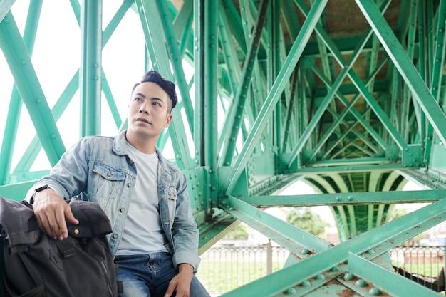 Jeune voyageur asiatique sérieux s'asseyant avec le sac à dos sous le pont vert et regardant autour