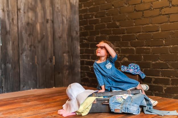 Jeune voyageur assis sur une valise avec des vêtements et regarde au loin
