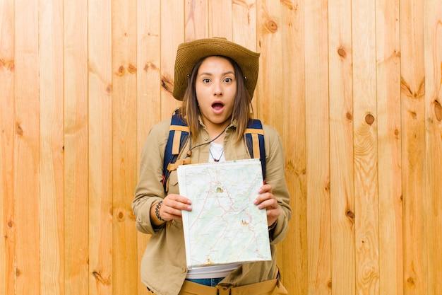 Jeune voyageur avec une carte contre le mur en bois